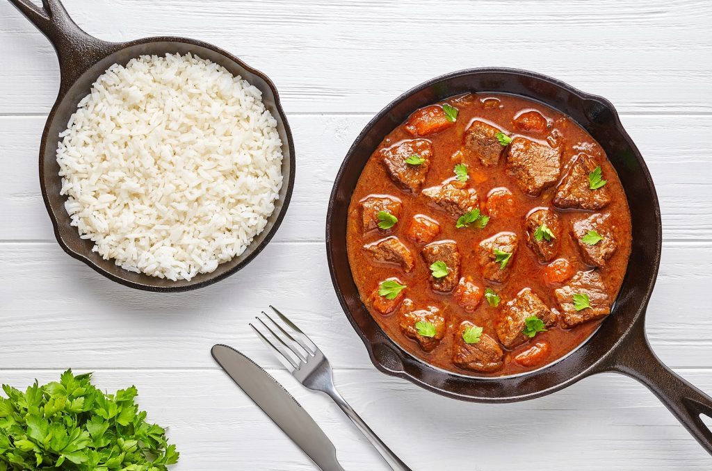 Goulash traditional Hungarian beef meat stew soup food dinner cooked recipe with spicy gravy sauce in cast iron pan served with rice and chopped parsley on white wooden kitchen table background.