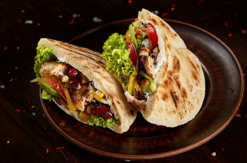 Tasty Jewish pita stuffed with grilled chicken, vegetables, beans, letucce on old-fashioned plate over vintage wooden background, side view, close-up, selective focus. Organic stuffed roll. Traditional Middle East cuisine. Fast food concept.